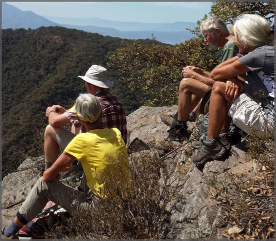 Four members of the hiking group looking down from the Mirador.